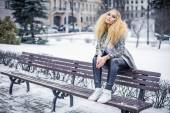 Golden haired woman on a bench — Stock Photo