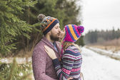 Young peaople are kissing in winter forest — Stock Photo