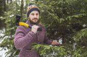 Lumberjack near the christmas tree in forest — Stock Photo