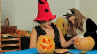 Woman with girl carving a pumpkin. — Stock Video
