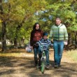 Happy Young Family With a Child On Bike Walking In Autumn Park — Stock Video #67470825