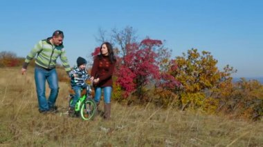 Happy Young Family With a Child Walking In Autumn Meadow — Vidéo