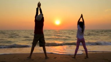 Boy And Girl Making Exercises On The Beach At Sunset — Stockvideo