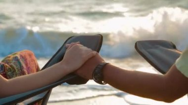 Loving Couple Holding Hands While Sitting On Outdoor Chairs At Seashore — Stock Video
