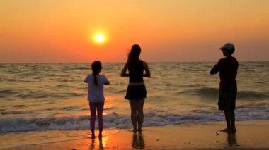 Three Children Doing Yoga Exercises On The Beach At Sunset — Stock Video