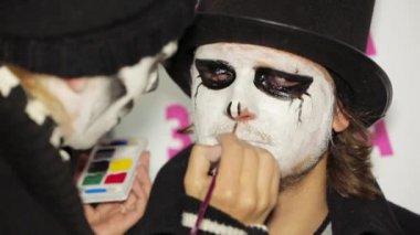 Молодая женщина применение темный макияж на Ман лицо на Хэллоуин — Стоковое видео