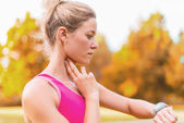 Attractive blond woman taking her pulse — Stock Photo