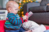 Cute baby opening a Christmas gift — Stock Photo