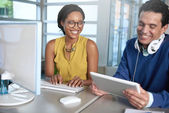 Two  colleages discussing ideas using a tablet and computer — Stock Photo