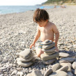 2 years toddler building pebbles tower on the beach — Stock Photo #55163717