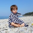 2 years boy in striped blanket sitting on the pebbles beach — Stock Photo #55163725