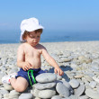 2 years toddler building pebbles tower on the beach — Stock Photo #55163727