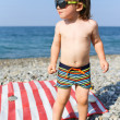 Happy little boy in sunglasses on stone beach — Stock Photo #55163905