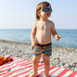 Happy 2 years boy in sunglasses on stone beach — Stock Photo #55163939