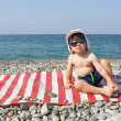 Happy 2 years boy in sunglasses sits on stone beach — Stock Photo #55164003