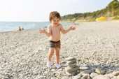 Happy toddler building pebbles tower on the beach — Stock Photo