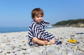 2 years boy in striped blanket sitting on the pebbles beach — Stock Photo