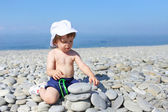 2 years toddler building pebbles tower on the beach — Stock Photo