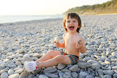 Happy smiling boy on the pebbles beach at sunset — Stock Photo