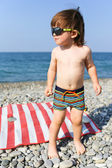 Happy little boy in sunglasses on stone beach  — Stock Photo