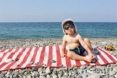 Happy 2 years boy in sunglasses sits on stone beach — Stock Photo