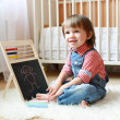 2 years toddler draws on the blackboard with chalk — Stock Photo #55965537