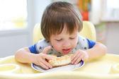 Little boy eats cheesecake — Zdjęcie stockowe