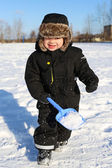 Lovely 2 years toddler running with shovel in winter — Stock Photo