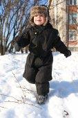 Lovely little boy in black snowsuits running in winter — Stock Photo