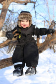 Happy 2 year toddler sitting on tree in winter — Stock Photo
