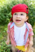 Lovely baby standing on grass and looking up — Stock Photo