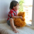 Lovely baby with plush bear looks out of window — Stock Photo #56737981