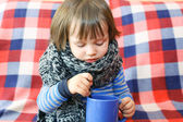 Lovely 2 years ill toddler in warm woolen scarf and cup of tea — Stock Photo