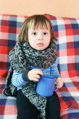 Sad ill 2 years child in warm woolen scarf with cup of tea — Stock Photo