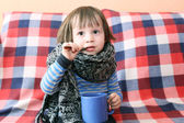 Lovely ill toddler in warm woolen scarf and cup of tea — Stock Photo