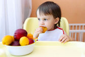 Baby eating fruits at home — Stock Photo