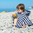 2 years boy in striped blanket sitting on the pebbles beach and — Stock Photo #56826005