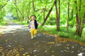 Lovely 2 years toddler boy in yellow trousers running in park — Stock Photo