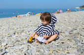 Little boy in striped blanket sitting on the pebbles beach and p — Stock fotografie