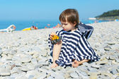 2 years boy in striped blanket sitting on the pebbles beach and  — Stock fotografie