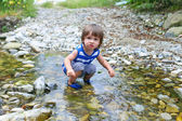 Little child standing in flashy river — Stock Photo