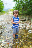 Happy little child standing in flashy river — Stock Photo