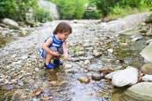 Lovely toddler boy plays with stick in flashy river — Stock Photo
