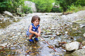 Toddler boy plays with stick in flashy river — Stock Photo