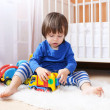 Lovely little boy in blue shirt plays cars at home — Stock Photo #57463587