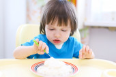 Lovely toddler boy eating quark  with sour cream — Stock Photo