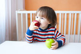 Lovely 2 years child eating apples  — Stock Photo