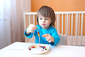 Little boy made multicolored beads — Stock Photo