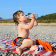 Lovely 2 years boy drinking water on the pebbles beach — Stock Photo #60042333