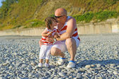 Father kissing his 2 years son in similar clothes on the seaside — Стоковое фото